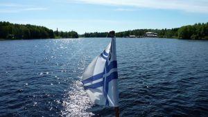 Suomenlippu liehuu Oulujarvella veneen perassa.