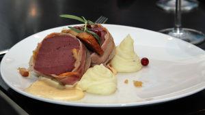 Kuvassa ravintolan ruoka-annos, pekoniin käärittyä hirvenfilettä ja perunamuusia.