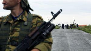 Sotilas vartioi alas ammutun koneen lähistöllä Ukrainassa lauantaina.