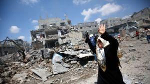 Palestiinalainen nainen itkee paetessaan Al Shejaeiya-kaupunginosasta Gazassa 20. heinäkuuta 2014.