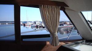 Veneen ikkunaverho ja taustalla satama.