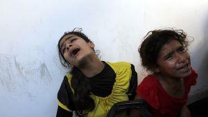 Tytöt itkivät YK:n ylläpitämään kouluun osuneessa iskussa kuollutta isäänsä Beit Hanunissa 24. heinäkuuta 2014.