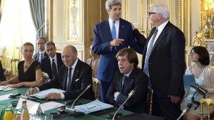 Yhdysvaltain ulkoministeri John Kerry rupattelee seisaaltaan saksalaisen kollegansa, Frank-Walter Steinmeierin kanssa muiden ulkoministerien istuessa pöydän ääressä.