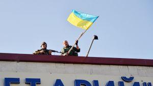 Ukraina-mielisen Donbass-ptalajoonan sotilaat heiluttavat maan lippua Lysychanskin kaupungissa 26. heinäkuuta.