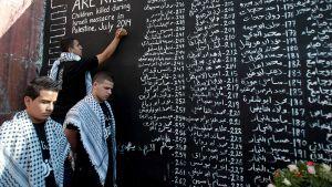 Palestiinalaisnuoret listasivat Israelin Gazaan kohdistuneissa iskuissa kuolleiden lasten nimiä. Kuva on otettu 28. heinäkuuta.