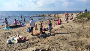 Ihmisiä Paltaniemen hiekkarannalla.