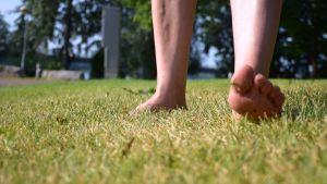 Nainen kävelee paljain jaloin kaupungin puistossa