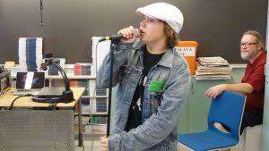 Eelis Saurio laulaa mikrofoniin bändileirillä. Erkki Rimpiläinen katselee taustalla.