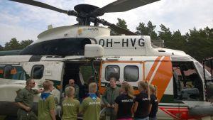 Partiolaisia Super Puma -helikopterin edessä