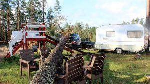 Autojen ja lasten liukumäen päälle kaatunut puu.