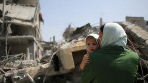 Palestiinalaisäiti katseli Israelin iskujen tuhoamien talojen raunioita Beit Hanunin kaupungissa Gazan kaistalla perjantaina.