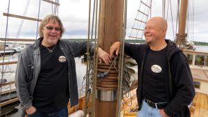 Esa Rautiainen ja Olli Ahonen nojaavat purjelaivan mastoon.