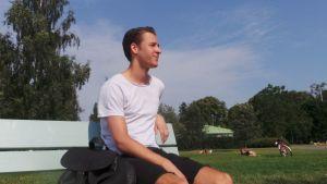 Nuori mies istuu puistonpenkillä Porin Kirjurinluodossa