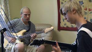 Kitaranopettaja opettaa nuorta poikaa soittamaan.