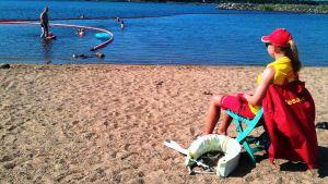 Kuvassa on rantavahti ja uimareita.