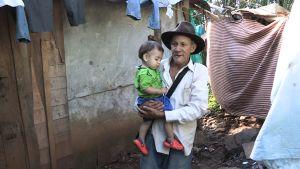 Maanviljelijä José Vicente Velasquez pikkulapsi sylissään.