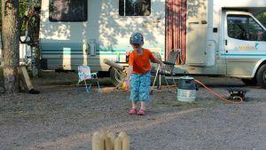 Lapsi heittää mölkkyä leirintäalueella