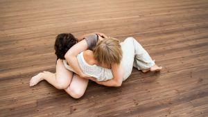 Tanssijat Nadja Pärssinen ja Anna Venäläinen halaavat Taivaltajat-tanssiteoksen kuvassa.