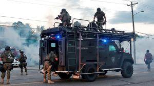 poliisi ampuu kyynelkaasua poliisiauton katolta ja auton vierestä