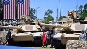 Barack Obama vilkuttaa vaimonsa kanssa tankkien välistä kävellessään.