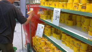 Mies ottaa juustopakettia hyllyltä Prismassa.