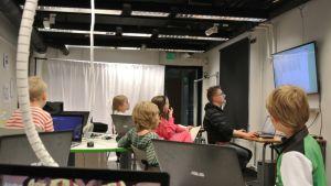 Lapset seuraavat mediapajalla opetusta kannetatvien tietokoneiden kanssa.