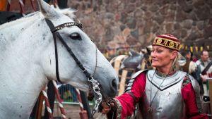 Haarniskoitu nainen pitää hevosta suitsista
