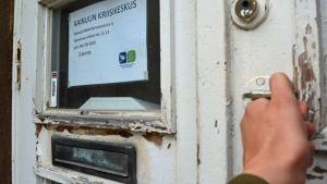 Käsi tarttuuu kriisikeskuksen oveen