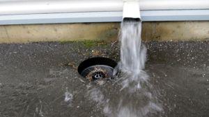 Vesi lorisee talon rännistä, mutta ei osu sadevesikaivoon.