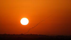 Gazasta Israeliin ammutun raketin taivaalle jättämä savu näkyi ilta-auringossa 20. elokuuta. Kuva on otettu Israelin puolelta rajaa.
