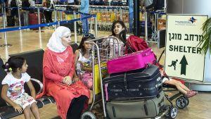Perhe odotti lentonsa lähtöä Ben Gurionin lentokentällä Tel Avivissa 21. elokuuta. Heidän vieressään oleva kyltti opastaa tien suojaan Hamasin iskujen sattuessa.