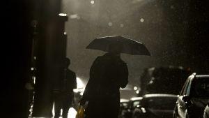 Ihmisiä sateessa.