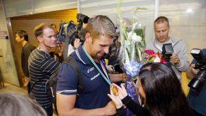 EM-kultamitalisti Antti Ruuskasen avovaimo Tuula Moilanen ihaili miehensä kultamitalia Helsinki-Vantaan lentokentällä joukkueen saapuessa EM-kisoista takaisin Suomeen maanantaina 18. elokuuta