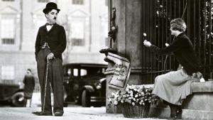 Charlie Chaplin katsoo sokeaa tyttöä joka ojentaa hänelle kukkasen.