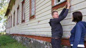 Ville Rautjoki esittelee rakennuksensa ikkunoiden koristelautoja. Vieressä Tuovi Rautjoki.