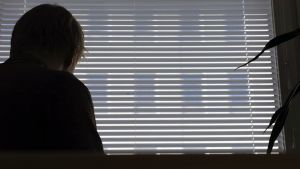 Nuori mies istuu ikkunan ääressä.