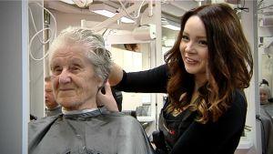 Parturikampaajaopiskelija leikkaa asiakkaan hiuksia.
