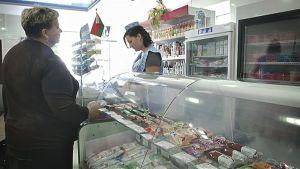 Keski-ikäinen nainen on kaupassa tekemässä ostoksia. Mustahiuksinen nainen tiskin takana.