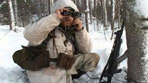 Lumipukuinen reserviläinen sotaharjoituksissa.