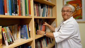 Nainen laittaa kirjoja hyllyyn.