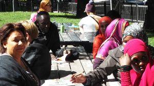 pakolaisia suomen kielen kurssilla puistossa