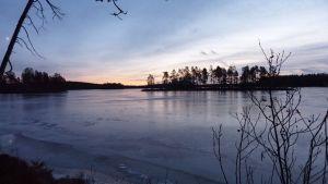 Jäinen järvi iltahämärässä.