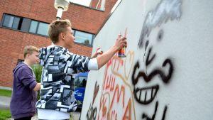Nuoret pojat maalaamassa graffiteja
