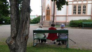 Kolme vanhaa naista istuu penkillä kirkon pihalla.