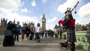 Mies soittaa säkkipilliä Westminsterin sillalla Lontoossa.