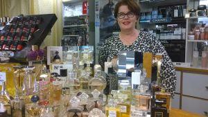 Kemikaliokauppias Marja Saarinen kaupassaan tiskin takana.