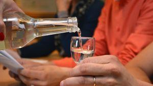 Pullosta kaadetaan kirkasta nestettä lasiin.