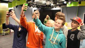 Nuoret ottavat kuvia älypuhelimella.