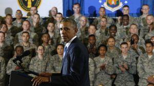 Barack Obama ja sotilaita taustalla.