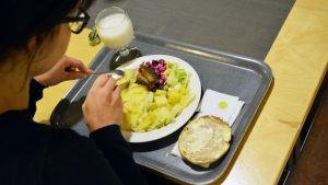 Nainen syö lounasta työpaikkaruokalassa.
